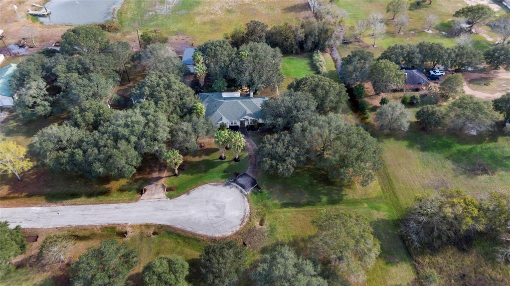 Unique property with both a gorgeous country setting and close proximity to shopping and main highway.  This one story home sits on approximately 1.5 acres of wooded beauty.  Spacious kitchen has a large island for all your cooking and entertaining.  Breakfast room will accommodate a large table.  Formal dining and formal living or study all with recent flooring updates.  Huge den with fireplace. Covered patio.  Split plan for privacy.  Master bath has handicapped accessible shower, jetted tub and double sinks.  In addition there is a 30x40 barn/workshop with 220 outlet, 2 10' rolling doors and heavy duty oscillating fans.  A wonderful place for auto buffs, carpentry or just to store the toys.  Fenced back yard.  Circle drive.  Lots of possibilities here.