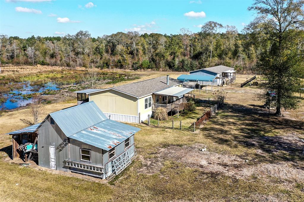 Here is your opportunity to own a large piece of country property yet be close to town! Over 10+ acres of unrestricted land with 2 homes on property, fully fenced, a 30'x20' barn, and (2) 20'x20' carports with attached storage sheds. Each home is unique yet, with the same 3 bedroom/2 bathroom open floor plan. Inside home #1 you'll find beautiful built ins, farmhouse cabinetry, an oversized kitchen island, tons of storage, and large walk in closets in every room. In home #2 you have a stone, wood burning fireplace, gorgeous floors, screened in back porch, walk in closets in every room, and it is handicap accessible. Each home has a large covered front porch perfect for enjoying your morning coffee and separate fenced in yards. The land is half cleared and has a 16' commercial quality entrance gate with a remote opener. On property is a 32x32 pen with 8' gate, (2) 600 gallon aerobic septics, a shared well, separate electric poles. Just 5 miles from 59! Home is not in flood zone.