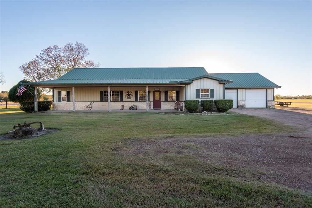 RUSTIC COUNTRY CHARMER!!!  This Ranch Style 2,387 sq foot home has 3 bedroom/2.5 baths with an office that could be used for a 4th bedroom and is located on 6.9+/- acres in Needville.  No HOA/Restrictions - bring your livestock and horses.  There is a custom built dog run with roof for your dogs.  Open floor plan is great for entertaining.  The property also has an attached oversized 2-car garage plus a large shop/barn with concrete floor and a carport for additional storage.  Don't miss this opportunity to move out to the country - easy commute to Hwy 59 or Grand Parkway.