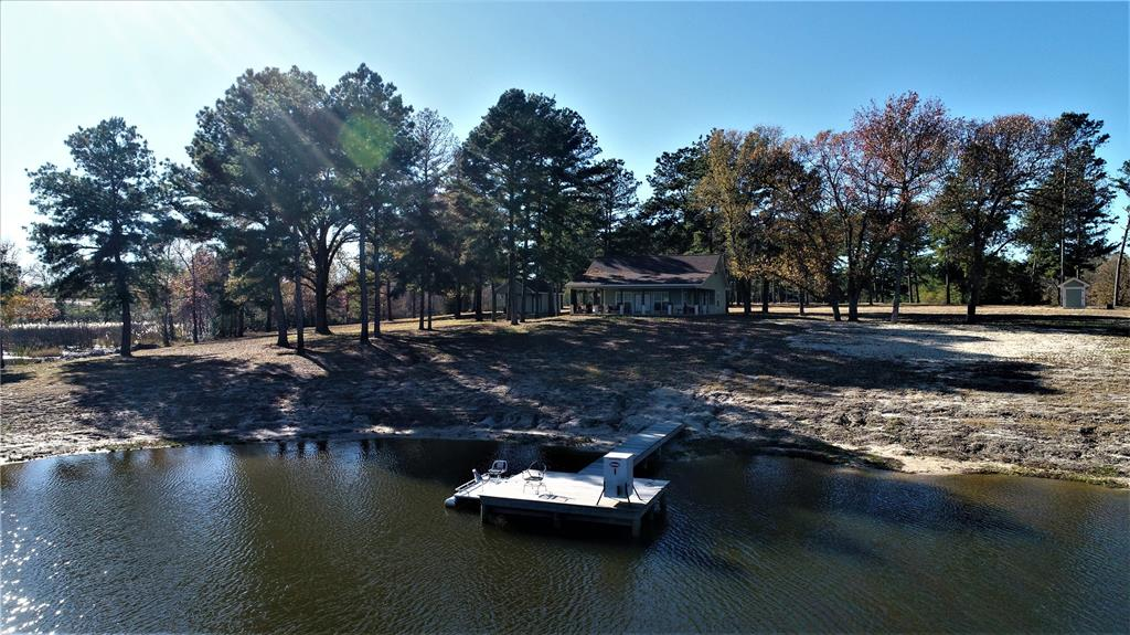 This secluded tract of land is the perfect weekend getaway for the avid hunter or someone looking to retire in a peaceful setting. This 2/2 home overlooks a 5-acre spring fed lake, stocked with bass and perch. This home includes granite countertops, a large kitchen island, vaulted ceilings, custom cabinets, and beautiful windows filling the room with natural sunlight.  Outside the home, you will enjoy the wrap around porches with a beautiful view of the lake. Just off the house is a nice, enclosed barn, capable of keeping tools, equipment, and utility vehicles. Under the overhang of the barn, is your very own fish cleaning station with sink and countertop space. On the land, there are plenty of spots to hunt with beautiful pine plantation, hardwoods, and pastureland. The owner reports abundant wild game, including whitetail deer, wild hogs, and waterfowl. If you are looking to get out of the city and enjoy the peaceful outdoors, this is the place for you!