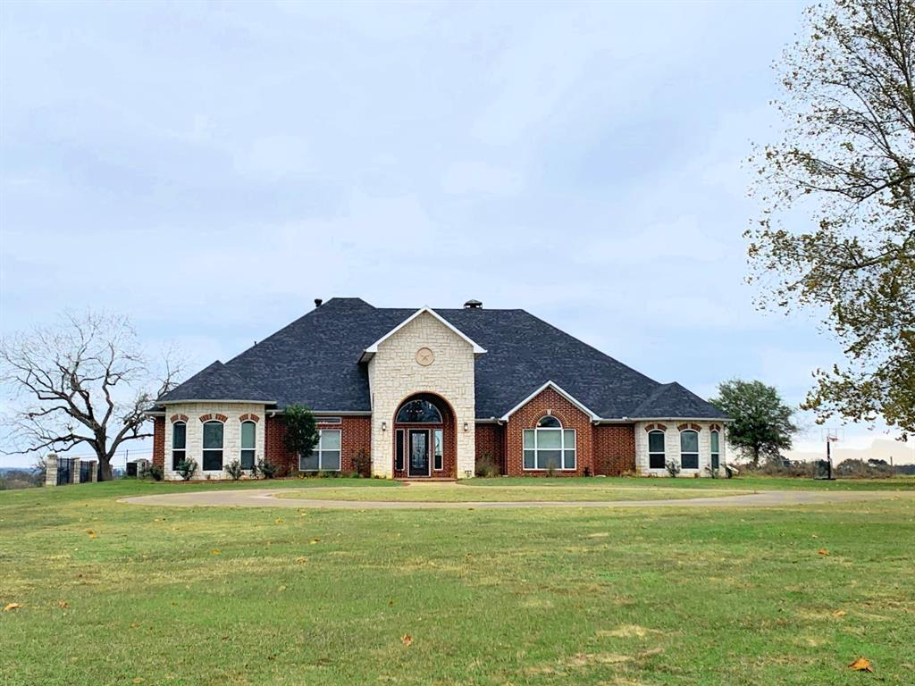 Custom home on 63 picturesque acres in East Texas! Formal dining area flanks the entry hall & gracious curved stairway. Large family room with stone fireplace & built-in bookshelves, kitchen, breakfast bar & breakfast area overlooking the saltwater pool. Large master bedroom with fireplace dividing the bedroom & sitting area. Master bath has spacious shower, tub, separate sinks, & two closets. Office with custom cabinetry. Three guest bedrooms, one with bath en suite & two with Jack & Jill, are located separately downstairs, along with utility room. Game room & media area are found upstairs with balcony overlooking the pool, complete with circular stairs leading to the patio below. Outdoor kitchen & pool bath complement the large patio. Fire pit is located adjacent to the pool area. Three car garage with sink & work bench. Fenced hay pastures, woods, & two spring fed ponds.