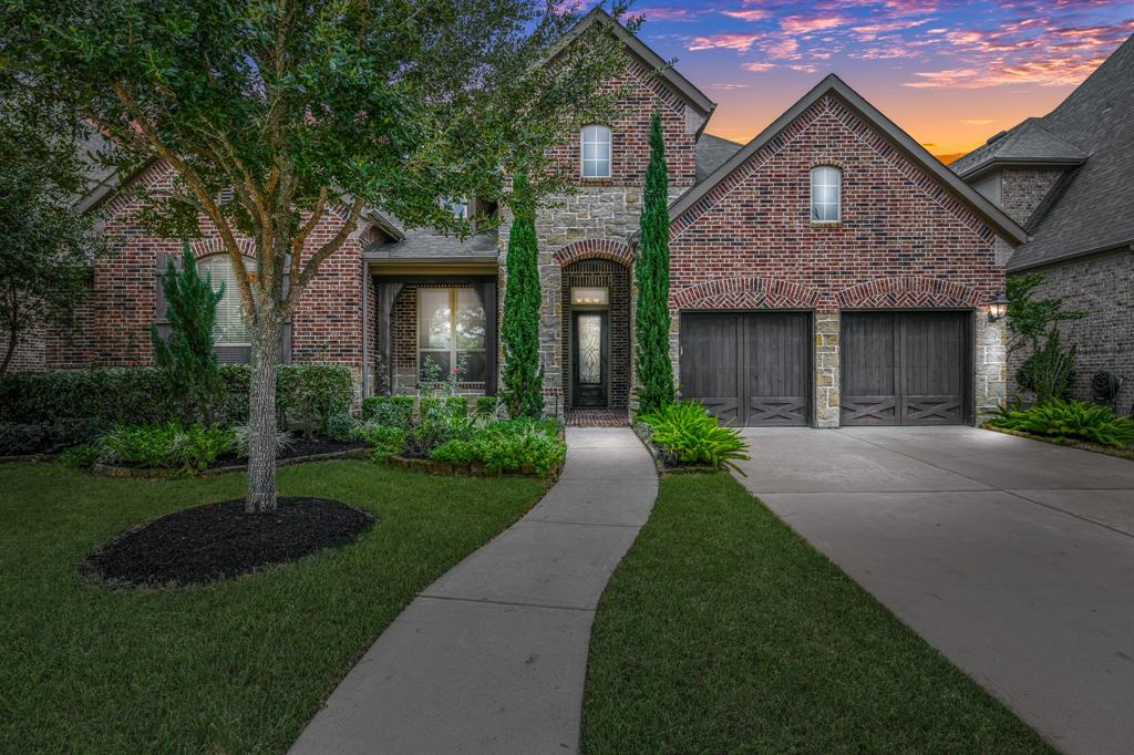 """Rare 1 story w/game room, study and 4 bdrms all with ensuite baths available in Aliana! Gorgeous built Highland Homes 4/3.5 w/ 3 car tandem garage and beautiful brick/stone elevation.  Incredible 19' ceilings in the living room w/ rich hardwood floors and Austin stoned fireplace plus cedar mantel.  Open kitchen-STUNNING with upgraded granite slab countertops, mosaic tile accented backsplash, SS appliances and walk-in pantry.  Game room w/upgraded wet bar/mini-fridge, study w/custom shelving, primary bdrm w/baywindow, and sitting area.  Primary bath is a """"spa"""" you won't want to leave!  Walk-in shower is appx 5'x4'. The walk-in closet is HUGE! Secondary bedrooms are big plus a walk-in closet. Dining room and butler pantry off foyer.  Most of the home features 12'-13' ceilings and 8-foot doors! 8' knotty wood front door w/iron accents and wood stained garage doors!  Fully landscaped in addition to an appx 16'x16' covered patio.  Watch 3D virtual tour! Zoned to Ft Bend ISD."""