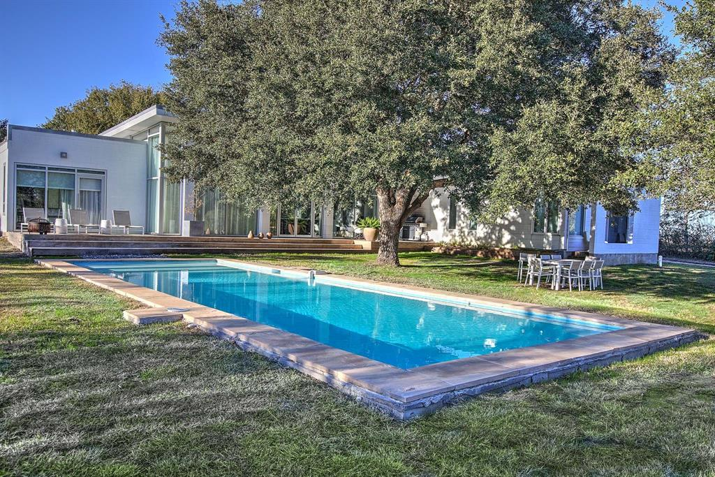 MODERN TURNKEY INCOME PRODUCING PROPERTY ON 5 ACRES/POOL Three bedrooms, study, three bathrooms  LOCATION: 20 minutes to Round Top, 15 minutes to Bellville, 90 minutes to Houston, 90 minutes to Austin Blurring the line between a work of contemporary art and nature, this unexpected modern design by studioMET architects, frames captivating views allowing the natural scenery to filter in from all areas and become an integral part of the design of the home. Impressive steel and glass doors usher you into a Great Hall that integrates the dining area and gourmet kitchen with modern cabinetry and Carrera Marble countertops.   Floor to ceiling windows surround the open concept living area that is dramatically perfectly designed for admiring the evening sunsets. Inside, 15-foot-high walls of windows offer a pass-through to the serene views of the modern pool, specimen oak trees and natural meadow surrounding the home. Includes All furniture-some Artwork.