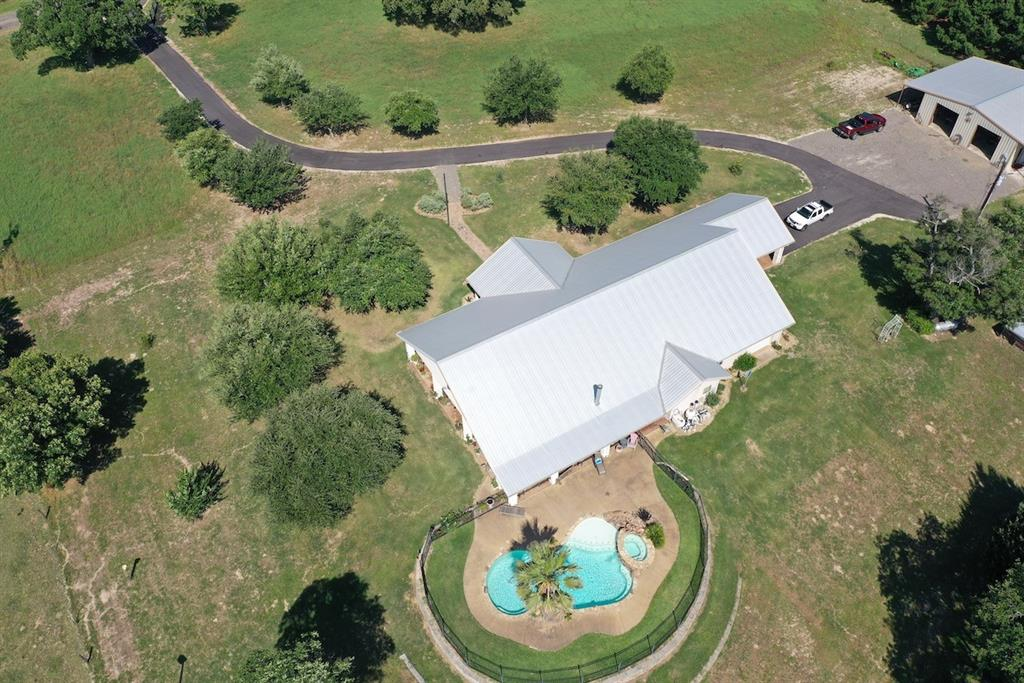 Rare opportunity to purchase a piece of heaven in East Texas. Custom built 3/3 Ranch style home on 35.32 Acres cross-fenced and improved, ready for livestock. Rustic ranch home with soaring ceilings, functional kitchen with granite and premium appliances, open to dining and living room. French doors lead to a full-length covered patio. Gunite pool with hot tub and private office off the master bedroom. Master bath is a must see with propane fireplace, garden tub, and over the top shower. Three car garage with plenty of storage and large metal shop with office, chicken coop, small garden, and cattle pens.