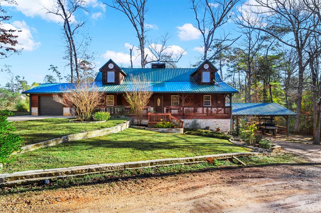 Come and get your own slice of beautiful country living in this amazing log home located on 4.62 acres. Enter into the entry/family room with high ceilings, a wood-burning fireplace, and beautiful archways leading to a Cook's Delight Kitchen, including granite countertops, stainless appliances, lots of cabinet space, and an eat-in area. A spacious primary bedroom with sitting area, His & Her sinks, whirlpool bath with separate tiled shower. Floor plan includes an overlooking balcony, loft, two spacious bedrooms, and full bathroom upstairs. Plenty of room to entertain-1 car attached garage plus an additional large carport, separate workshop, mother-in-law quarters or college student's place with living/kitchen/bedroom/full bathroom upstairs. Downstairs- 30x16 man-cave/she shed including a full bath. Outside you will find numerous fruit trees, decks surrounding an above ground pool, and hot tub. Buy now and take advantage of the historically low-interest rates! Call for your showing!
