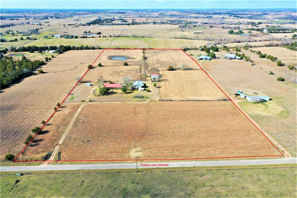 """Estate property being sold """"AS-IS, WHERE-IS"""".  Needs work but has lots of potential.  Good elevation, no flooding. 20 ACRES with great views on a paved road west of Bellville. Currently under Agricultural exemption for cattle grazing and hay production. 1-story Home built in 1987 of concrete block with metal roof 3 bedroom, 2 bath, island kitchen (granite countertops, solid wood cabinets, gas oven/range, refrigerator, dishwasher, pantry), large living area with wood burning stove, beamed ceilings plus large covered porches.   2nd home is a Mobile Home with 3 bedrooms, 2 baths. Both homes with central heat and air, propane tank,  Private water well and septic. Fruit trees, Barn with 2 stalls and pens (great set up for 4-H Projects, Tool Shed/Shop, Pond, mostly fenced and cross fenced with water to pasture, American Flag pole. Main house water leak in the bathroom that caused damage to the sheetrock and floors in the 2nd & 3rd bedroom. Water is currently turned off in the bathroom."""