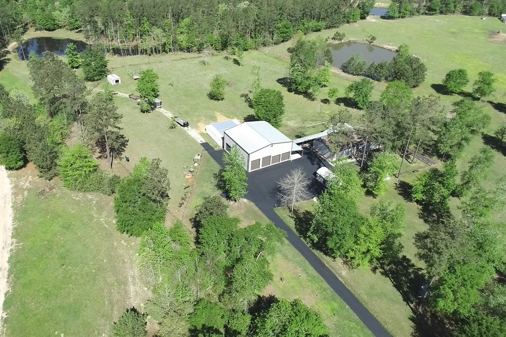 Get out of town and into this gorgeous recreational/industrial Ranch getaway!  This 38 acre gem is located in the heart of the Sam Houston National Forest. Property borders the forest on 2 sides and offers a multitude of possibilities. Pull out your ATVs and roam around on the open spaces accented by two 20 foot ponds and a wooded area designated for hunting. Graze your animals, harvest your own food, or even start your own business in the existing immaculate shop on property. This tract features a great country home with multiple open porches and wood deck that is perfect for family get togethers and parties. Infrastructure costs can be worrisome upon purchase... Not to worry.. This tract comes with an existing dual well set-up, septic, and irrigation system. Electricity is also already in place for a smooth turn-key move in.  Do not miss this unique opportunity! Book your appointment today.