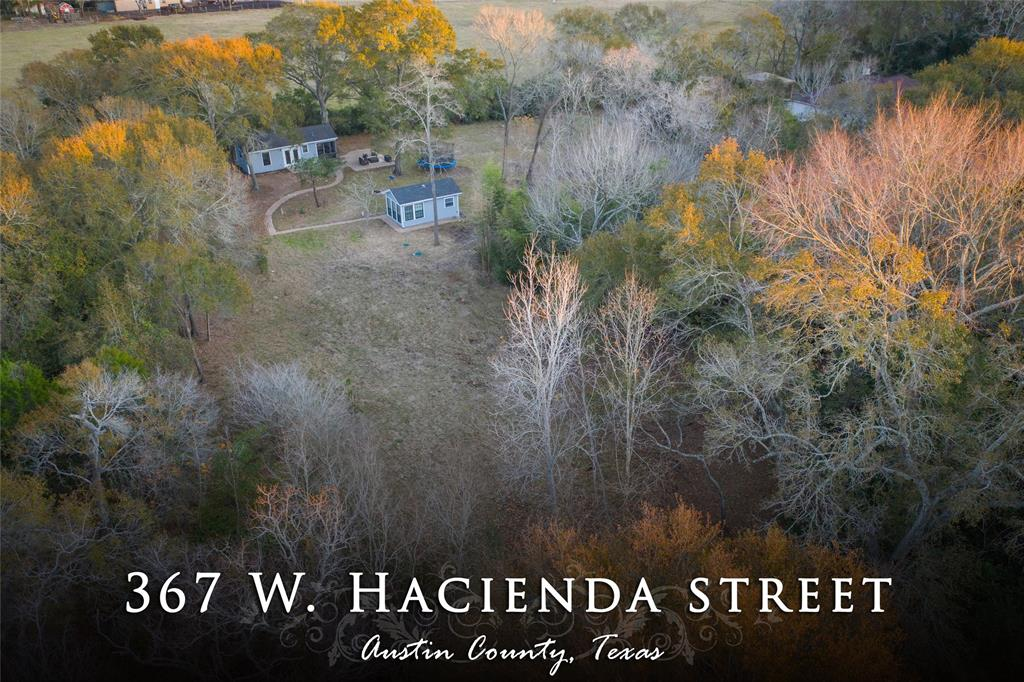 STILL CREEK  Lovely wooded acreage with two small cabins. This property is located very close to the town of Bellville but still quiet and peaceful. A deep creek divides this property and offers a scenic shady addition to woods and open areas around the cabins. There are several trails in place for hiking and ATV exploration. In addition to many large hardwoods, there are beautiful Cypress trees near the creek . So many possibilities for the land. The cute cabins are freshly painted and main cabin has a screened in porch area, bedroom, bath, and kitchen, breakfast combination. A nice patio is attached to the porch. A small fire pit is positioned near the patio. The additional cabin has another bedroom, full bath and area for stackable washer and dryer set. Cabins are connected by a long sidewalk and flowerbeds. Cutest place ever for weekend escapes! Come see!