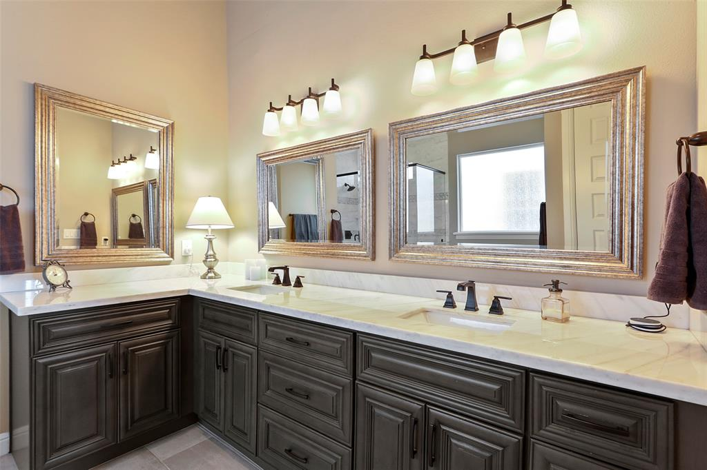 The primary bath features dual vanities with luxurious finishes