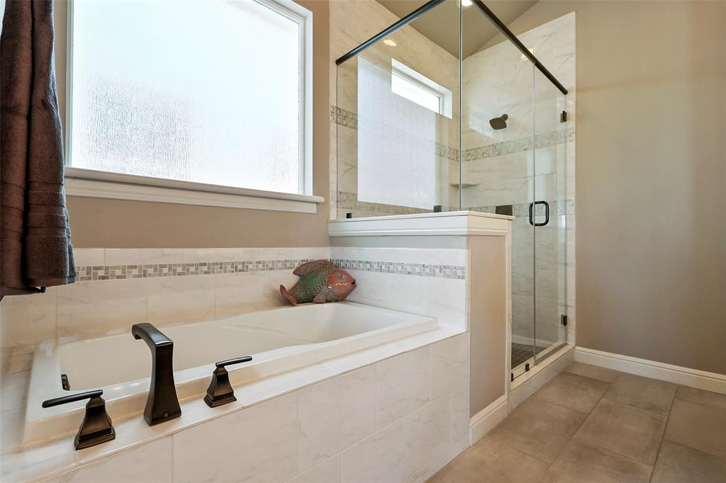 The primary bath features a large shower with separate tub