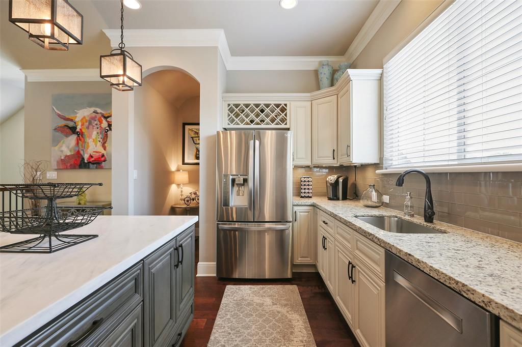 The kitchen features marble and granite counter tops, glass tile back splash and stainless steel appliances