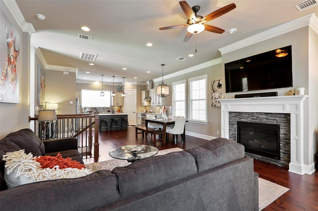 The living space features wood floors, crown molding and recessed lights