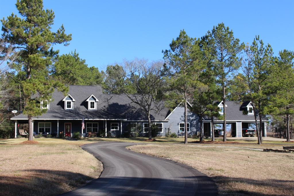 Delightful modern ranch home on 12+ secluded acres in Montgomery ISD.  3,021 sq. ft., built 2010, one story, 3 bed 2½ baths, recently painted inside and out. Wide plank pine floors throughout recently sanded and re-stained. Island kitchen upgraded with quartz countertops, soft closing drawers and cabinets. Sitting room off primary bedroom with wood burning stove. Primary bath with claw foot tub, double sinks, separate shower. Family room has extensive cabinetry for craft projects.  Attic area framed in as potential fourth bedroom.  8 ft wide covered porches on three sides.  4-car carport. Asphalt circle drive. Shop building beside the home with power, two roll up doors. Land is rolling, part open part wooded, no flood plain, wildlife exemption. Light restrictions in place, horses allowed.  Easy access to shopping, dining and medical.  Close to Lake Conroe and Sam Houston National Forest; about half-way between Houston and Bryan/College Station.