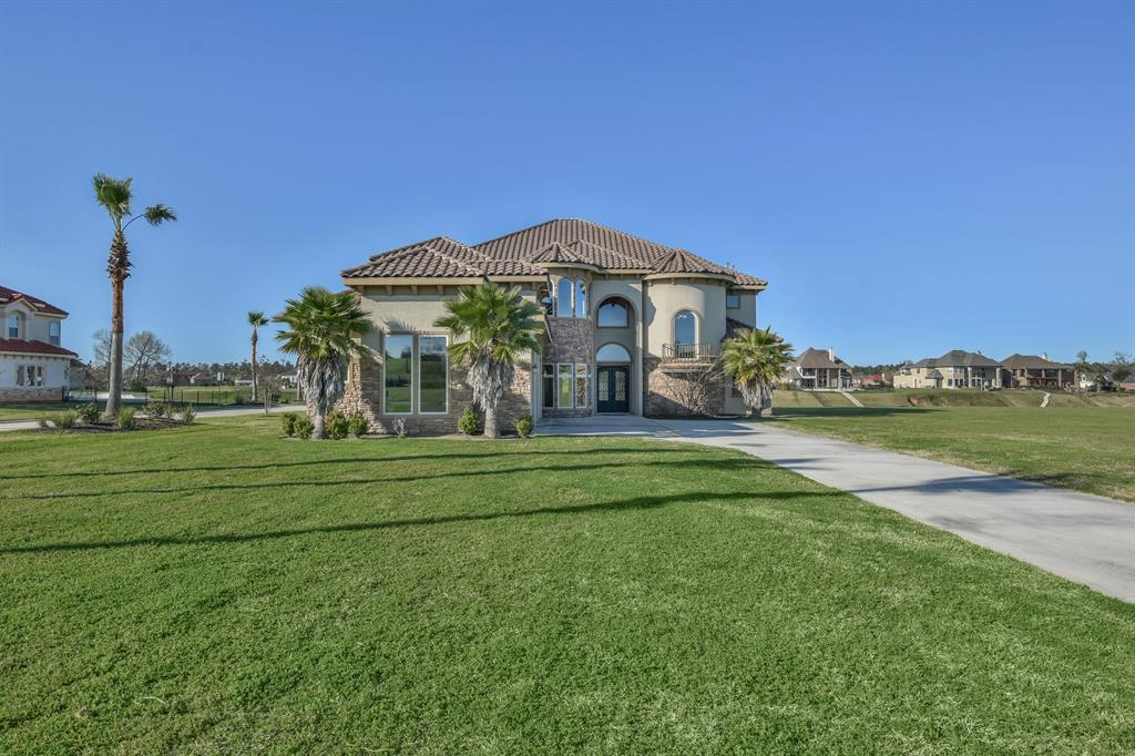 Enjoy lake living in style in this stunning Mediterranean style custom home on Lake Conroe.  This beauty is nestled in the manned gated community of The Island at Grand Harbor. Impressive curb appeal on a private corner lot with no neighbors next door, behind or across the street. Gorgeous stucco and stone exterior with tile roof.  Functional floor plan that flows beautifully from 2 story foyer with spiral, wrought iron spindles staircase to formal living and dining, downstairs study and great room that opens up to the expansive chef dream island kitchen and breakfast. Intricate millwork throughout the house, Soaring 12' ceilings down, Expansive windows create inviting views of the fantastic outdoor space. Enjoy the outdoor living and breathtaking views of the lake on the outdoor patio with summer kitchen and fireplace or the upstairs oversized balcony. Too many fantastic features to list, must see this great home to appreciate! NEVER FLOODED, low tax rate and exemplary Montgomery ISD.