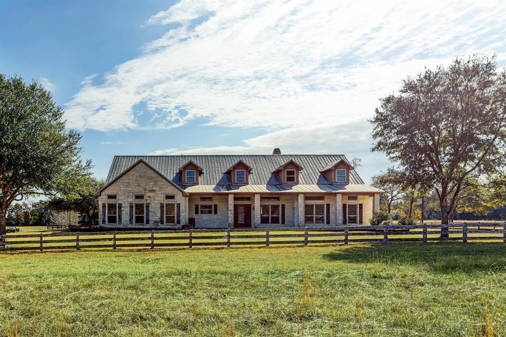 Country living at its best, Big Dog Ranch on 13 pristine acres right outside of Bellville. Only 65 miles from Houston. The charming Austin stone house (3252 sf) with 4 bedrooms, 3 and 1 half bath home over looks the fully stocked pond. The Texas charm continues as you enter thru the beveled glass front door etched with the Texas Star to Cypress wood paneled walls and 16 ft cathedral ceiling in Living/Dining Area. Ceiling is supported by cedar beams with hand cut metal braces. A limestone fireplace is surrounded by built-in bookcases. Slate floors throughout living/dining/kitchen area. Gourmet Kitchen with stainless steel appliances, double ovens, 5 burner Kitchen Aid induction cook top, pine cabinets, Custom made metal farm sink and exhaust hood with Clavos accents. Glass French doors lead to back covered porch. Metal Barn (1500 sf) with concrete floors has 3 roll up doors and upstairs storage. Metal horse stalls with fenced turn out pasture. Fishing pier. Ag exemption in place.