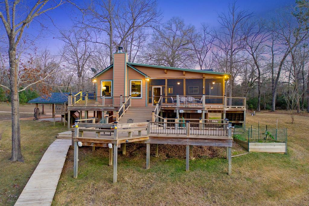 STUNNING, ONE-OF-A-KIND, WATERFRONT ACREAGE!  ENDLESS POSSIBILITIES!  Private retreat, family compound, vacation rental, residential development, commercial development...you decide.  41 ac unrestricted with approximately 1400 linear ft of deep waterfront and partially fenced.  Protected, with open water views limit shoreline maintenance.  Property has old growth and new growth timber, hardwood and pine, stocked natural spring pond, multiple recreational trails.  Enjoy the abundant wildlife from deer, rabbits and squirrel to a multitude birds.  Quintessential lake cottage with finishes you would expect in any well-appointed home.  Open-concept for easy entertaining, spacious screened porch for year round enjoyment, multi-level decks, basketball goal with half-court, fishing pier, boat ramp, boat house w/boat and jet ski lifts, whole house water softener, Spider-B-Gone system.  Property is fenced at the street w/gate for privacy.  Call to arrange a tour today.