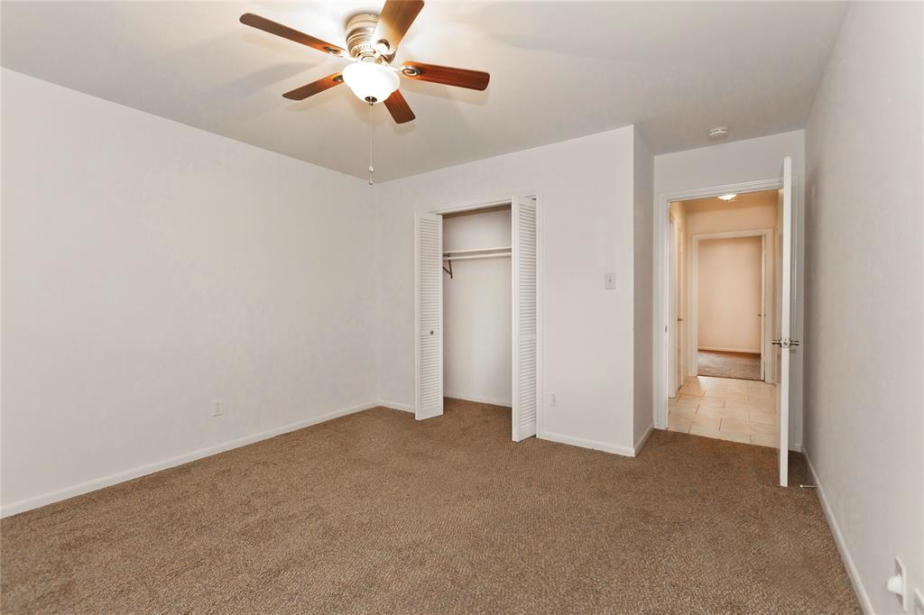 The third bedroom, freshly carpeted like the others, looks over the shaded back yard.