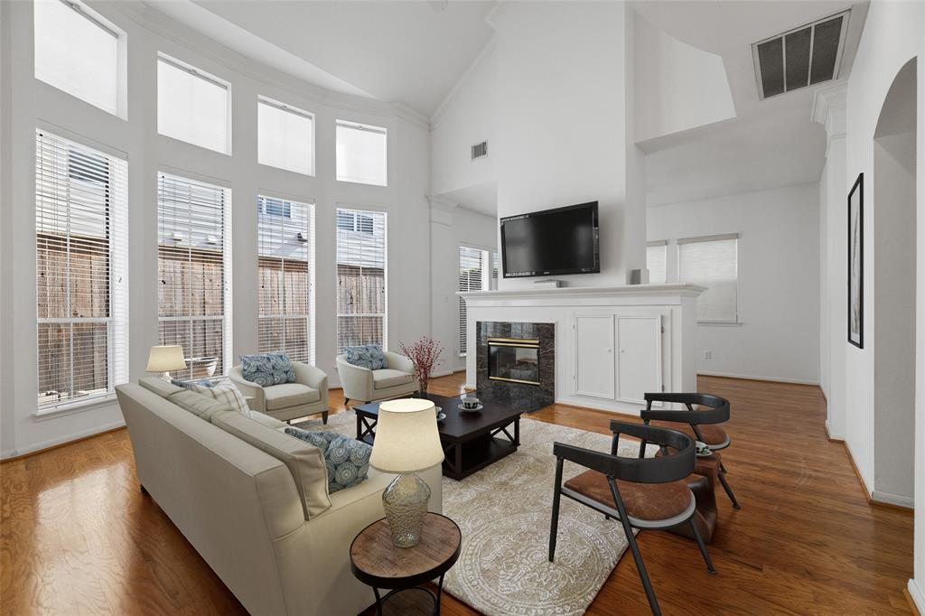 The spacious living space features a soaring ceiling, wood floors and lots of natural light.  This photo has been virtually staged.