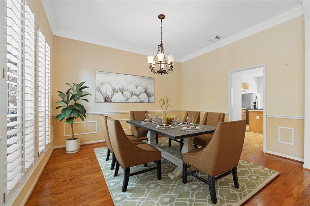 The dining space is large enough for a six or eight person dining table and features wood floors and plantation shutters.  This photo has been virtually staged.