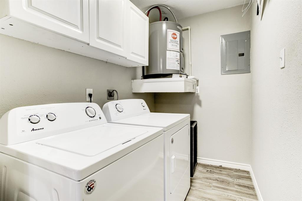 The laundry room with a side-by-side washer/dryer set up, and extra cabinet space.