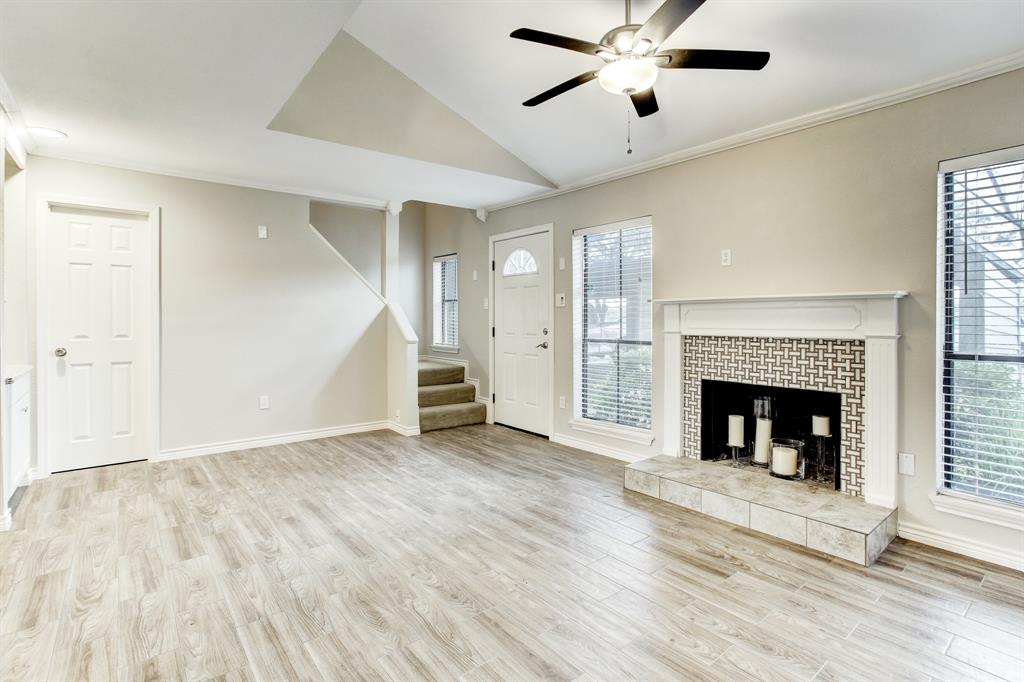 Enter the home into its very spacious living area with beautiful tile flooring and a wood burning fireplace.  The door to the left is to the half/guest bath, and the stairs lead to the bedroom suite.