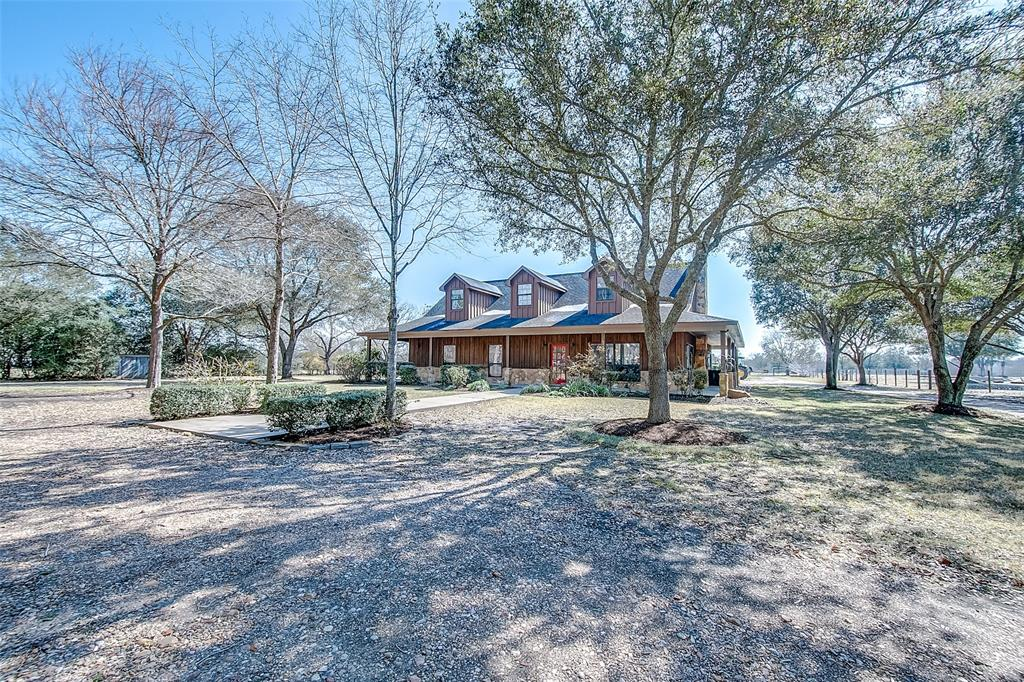 RARE OPPORTUNITY to own a beautiful ranch home on 7.18 acres with a 2 acre pond stocked with catfish, bass, and perch; a floating dock and beach entrance. This beautiful home has 5 bedrooms and 3 1/2 baths and a small bonus room, cypress wood floors, new paint, new carpet.  Includes out building, workshop, covered parking for 6 vehicles, fenced and cross fenced, and has electric gated access. No HOA or MUD taxes and No Restrictions.  City water, sewer, and gas.  Relax under the 80-90 year old live oaks in your HUGE back yard! Say YES to the address! Watch the video!