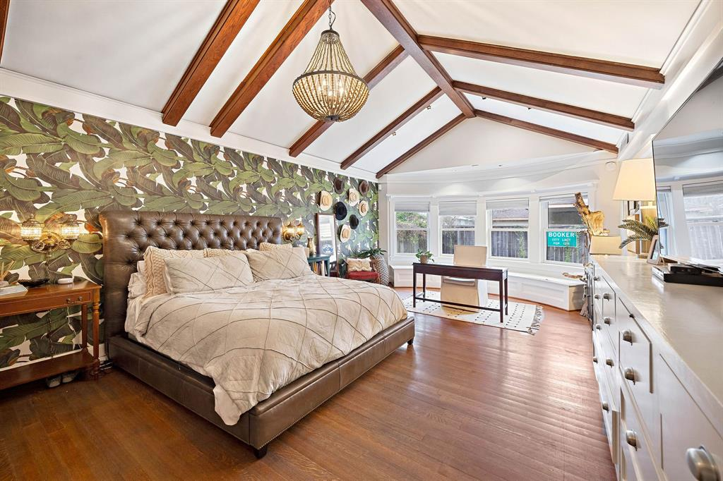 Primary bedroom with vaulted ceilings, exposed beams and a full length window seat.