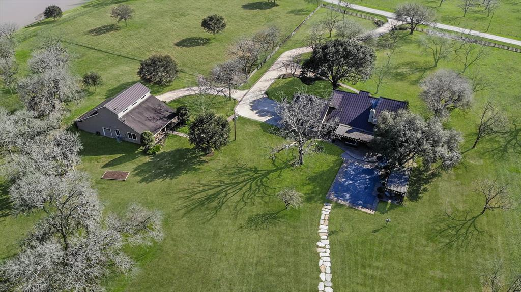 Gorgeous luxury home on 10.92 acres in Richmond. Enter through the gated access to your fully fenced, immaculately maintained property. Main home boasts travertine floors down, wood floors up, custom handcrafted metal & glass french doors,4 Lenox AC(2017), Roof(2012),Pool Equip(2017) & sprinkler! Formal dining w/natural dyed grass cloth accent wall. Family room w/2 story ceilings, wood beams & fireplace. Kitchen w/Justin & Co custom soft close cabinetry, double ovens & Jenn-Air stainless appliances. Master bed w/ensuite bath w/double sinks, & Carrara marble counters. 3 Bed & 2 bath up along w/an oversized game room. 3.38 acre Pecan Grove w/irrigation system. Large pond w/seating for gathering. 1600 Sq Ft barn & loft storage w/updated 800 Sq Ft Barndominium featuring stained concrete floors, spacious living room, 1 bedroom, updated bath w/shower, & 1 car garage! Barn has additional 20'X40' upstairs storage area. Heated pool and outdoor oasis w/ample sitting area great for entertaining.