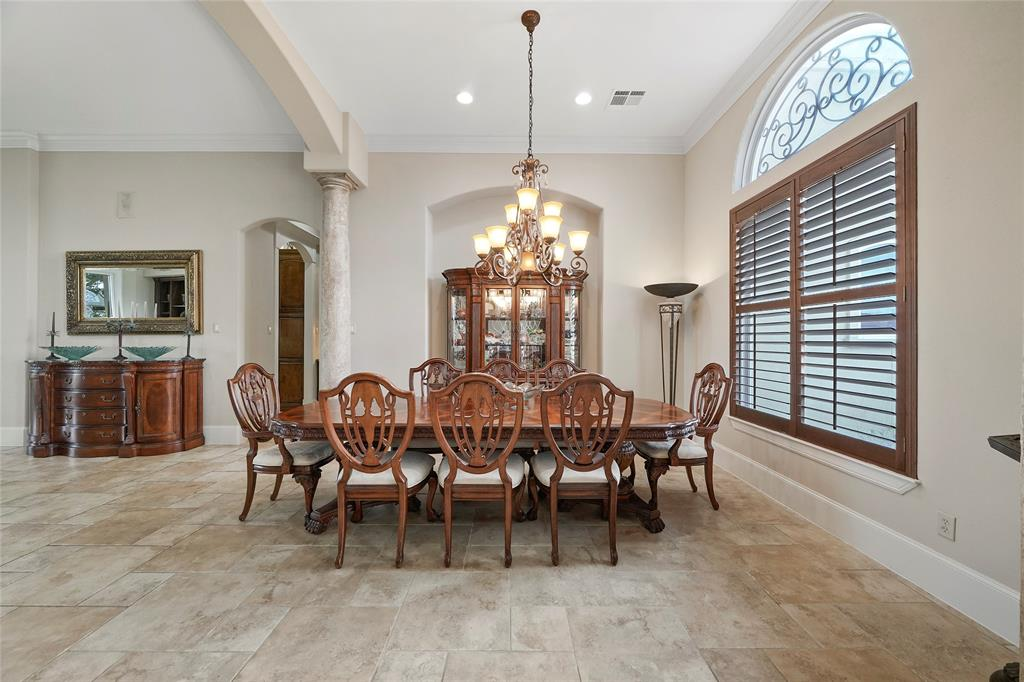 Formal dining room is open to the foyer and living room. The large window with custom plantation shutters overlooks the front yard. Notice the custom wrought iron detail in the arched window.