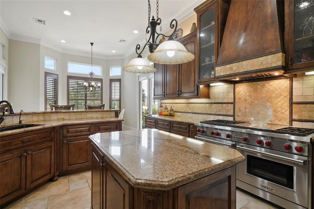 Glass cabinets, center island with beveled corners, undermount sink, under counter lighting are just a few of the custom features of the kitchen.