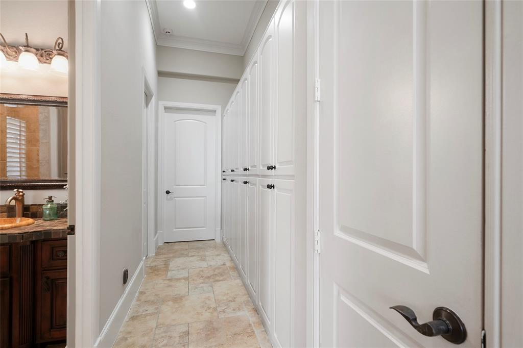 Hallway leading to the first floor full bath and laundry room. Look at all of this storage! A wall of cabinets for shoes, backpacks, work bags, sports equipment, and coats! Finally, a place for everything!