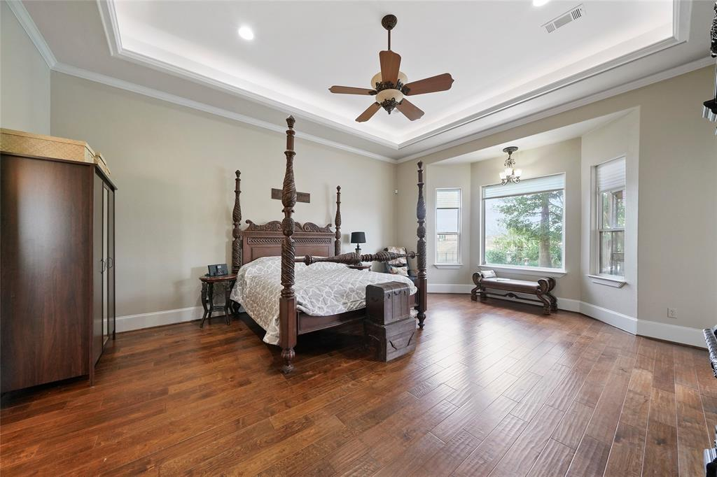 The master bedroom is large enough for a separate sitting area near the bay window that overlooks the backyard. The wood floor, tray ceiling with ambient lighting and crown molding are a few custom features.