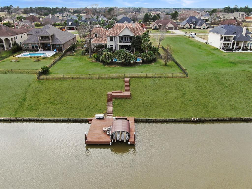 Large fenced backyard and stairs with landing to the large boat dock.