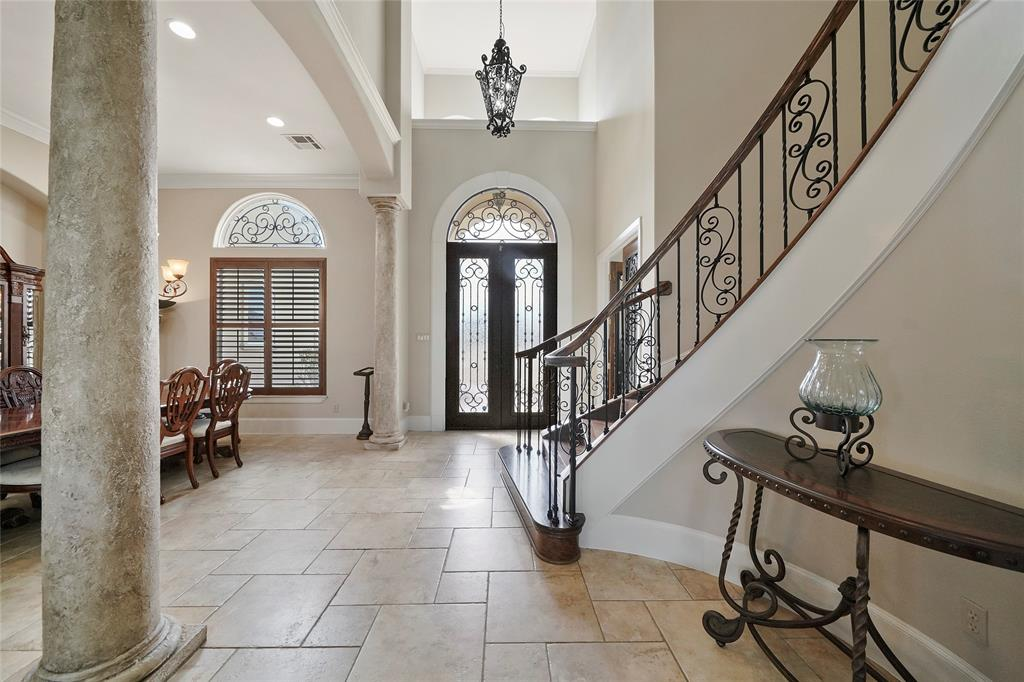 Double iron doors with custom wrought iron inlay and the curved staircase trimmed with wood and wrought iron creates a grand entrance.