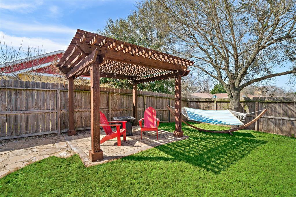 Custom pergola and hammock in backyard. Mature trees.