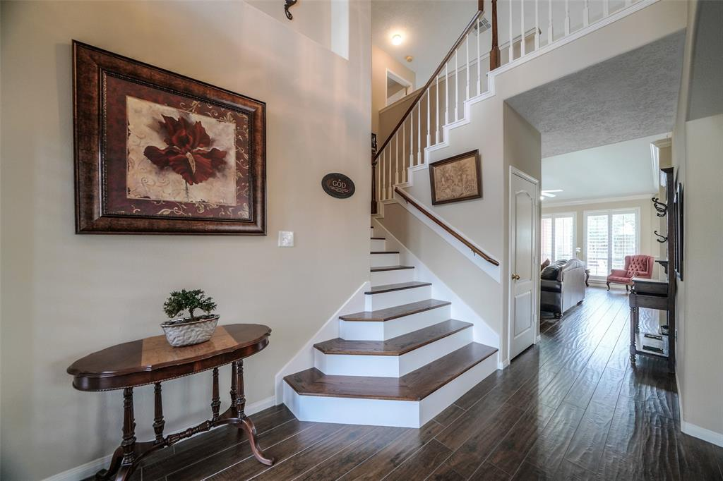 Upon entering the home, you'll see the staircase leading to the secondary bedrooms. The stairs were replaced with wood in 2017.