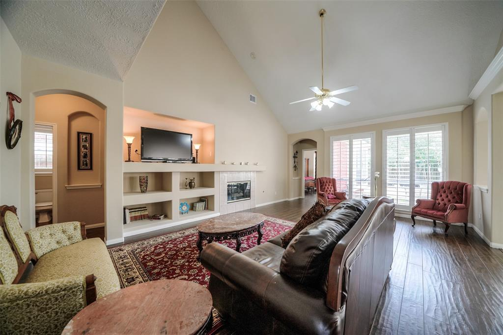 This large family room has versatile shelving for endless decoration possibilities, and soaring ceilings. The guest half-bathroom is located to the left, past the hallway.