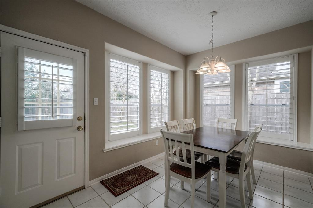 This amply sized breakfast area easily fits a six-person table and has views of the large backyard.