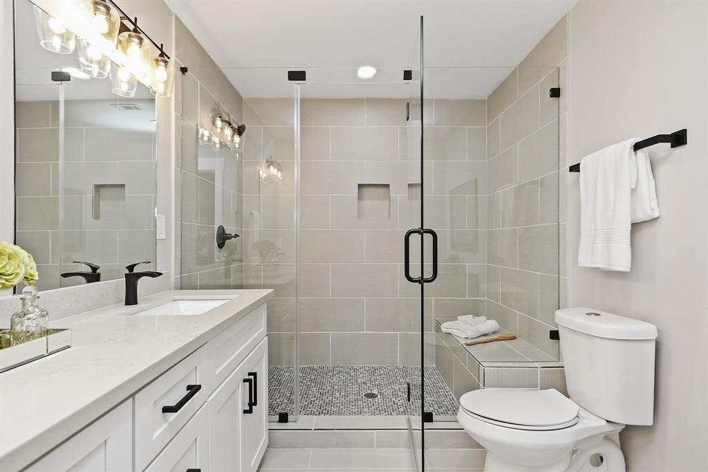 A closer look at the step in frame-less glass shower stall with bench seating.