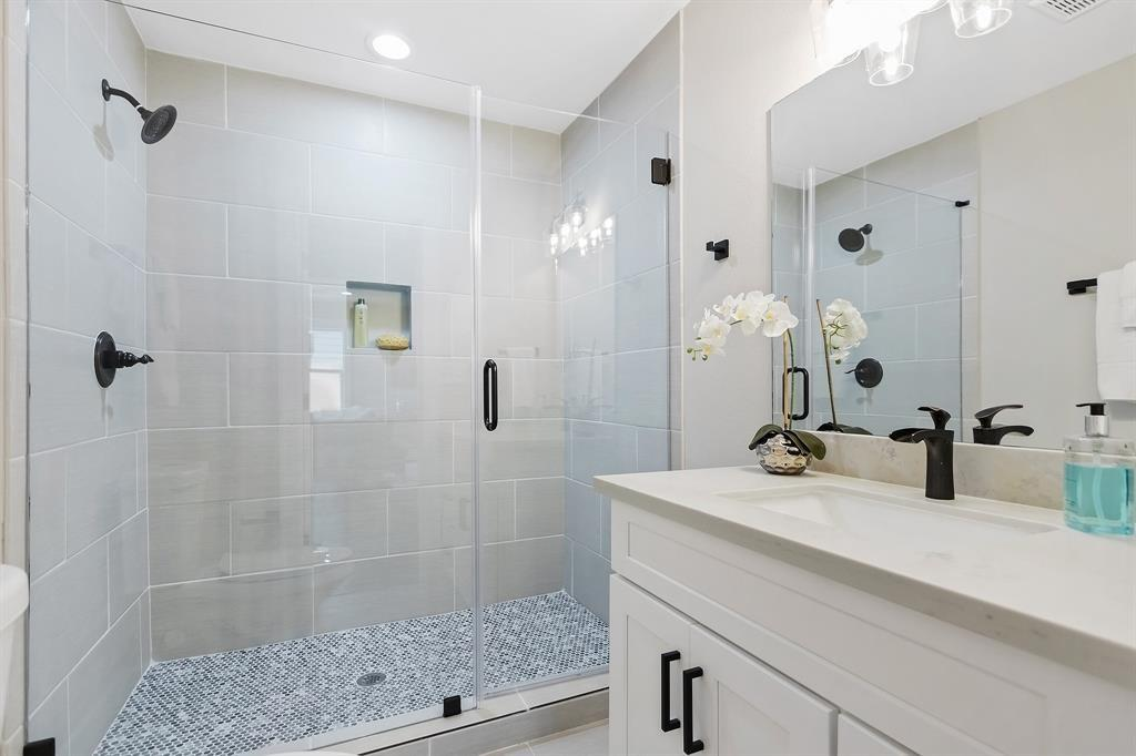 The first of two full guest/secondary baths, with similar finishes to the primary bath, sits between the two bedrooms off the living area at the front of the home. Another amply sized step in shower stall.
