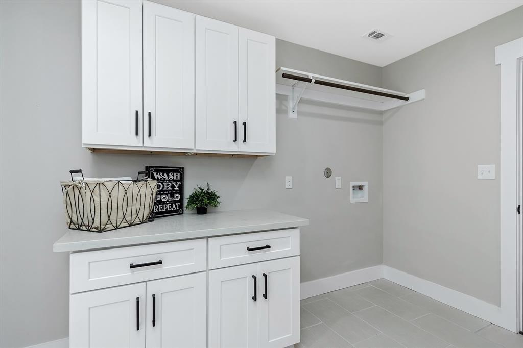 A very spacious utility room outside the primary suite includes cabinet, counter and hanging space. It's finished just as beautifully as the rest of the home!