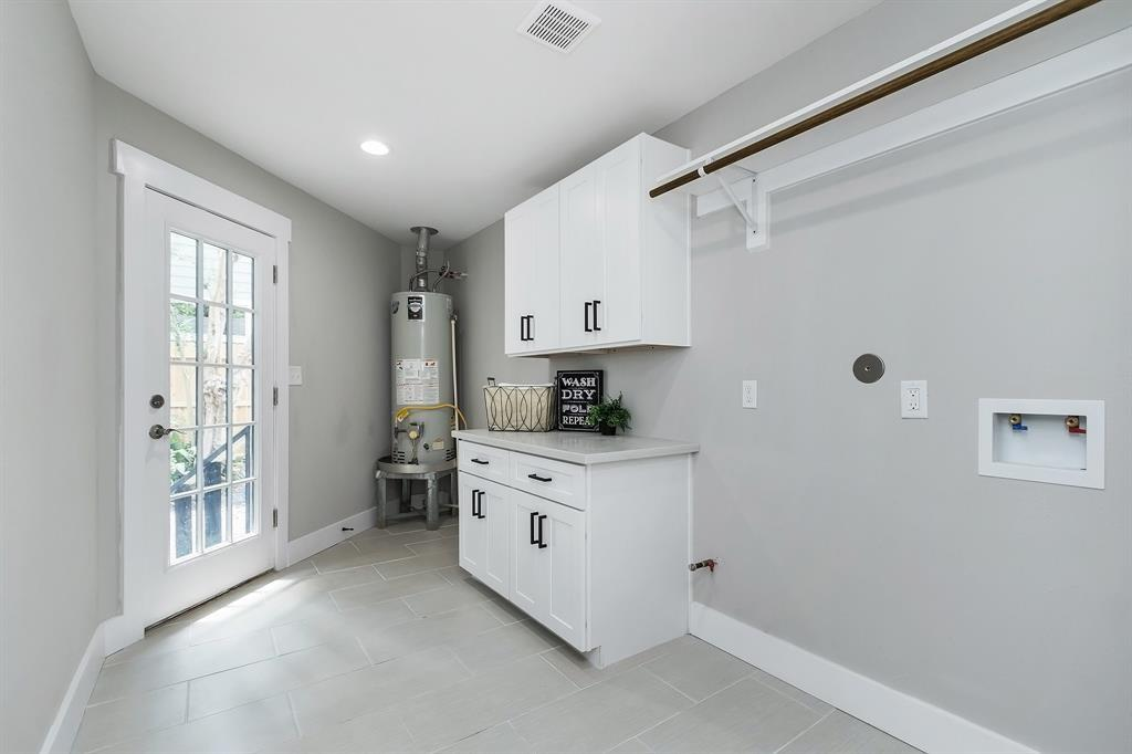 This angle shows just how spacious the utility room is, including a side-by-side washer/dryer set up. The door leads to the driveway and garage.