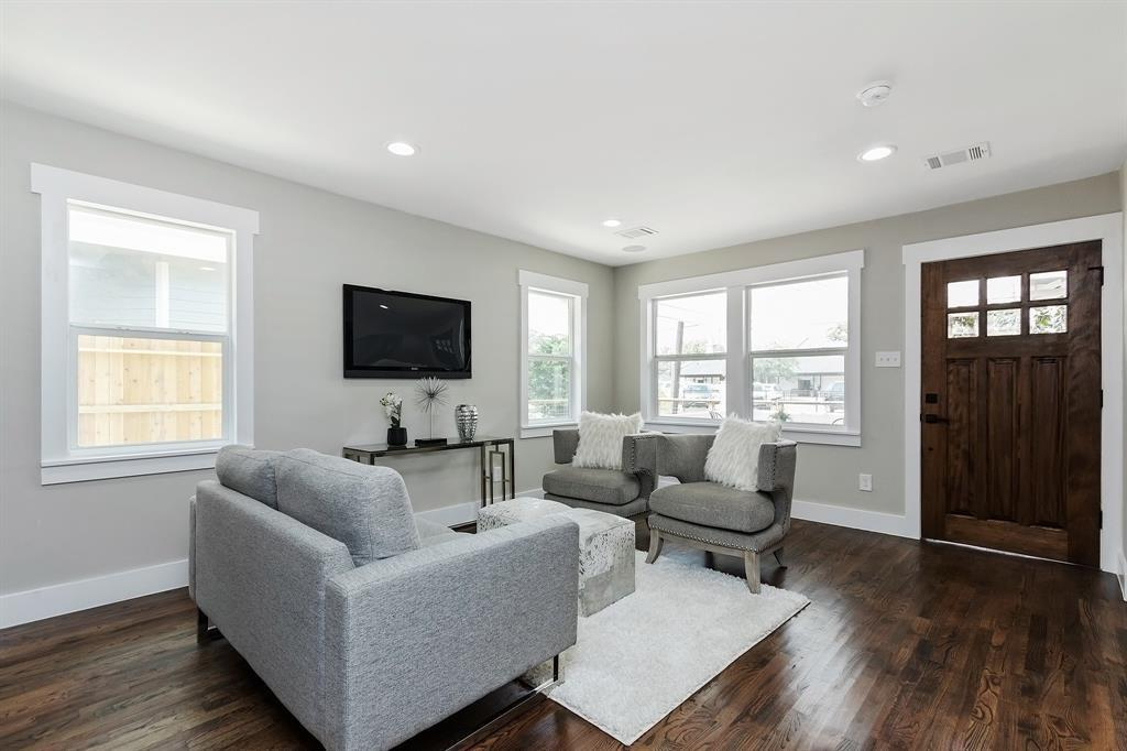 The living area sits just inside the front door. These gorgeous hardwood floors run throughout the home.
