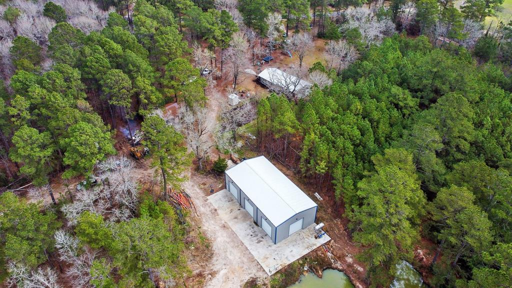 Welcome to your home in the country !! This hidden gem has so much to offer. The 1747 sq. ft home sits on 6.94 acres that's nestled in San Jacinto County in the city of Oakhurst. This property has so much to offer, from the secludedness, trees, privacy, pond, open garden area, livestock areas, and not to mention the HUGE metal building the seller had built. The metal building is a 40x75, boasts 5-14x14 roll up doors, 6 inch concrete slab, gutters, completely insulated, and 12 LED lights (20k lumens) to brighten the place up as well as being completely lit on the outside. There is also a 25x25 workshop on the acreage to have as extra storage. Building also has 2 accessible driveways to get in and out. The home itself features 3 bedrooms and 2 full baths, newer roof, insulated windows and a 4 ton AC. Original part of the home was roughly 950 sq. ft and sellers added the rest as an add on. This is a must see !!