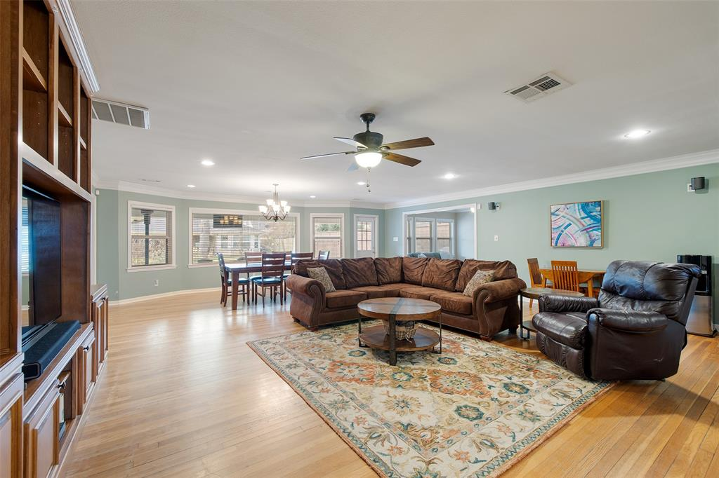 The spacious open living spaces feature wood floors, crown molding and built-in storage.