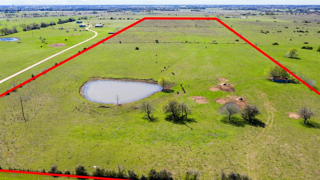 This is truly a gem of a piece of property. There is no way to show it to you in pictures but from the front gate to the trees and pond is a hill that you climb. It is the PERFECT spot to build a home not only looking over the pond but it has an amazing view over the Bernardo, Cat Spring Area. It's quiet down this county road with green grass and cows as far as you can see but the view from the back of the property, you can faintly see I-10 which means you get the best of both worlds. You will enjoy the country life but are convenient to I-10 to get to work in the morning or head to town for errands. This property is perfectly rectangular and already has an electrical line that runs through the property. This property has been in the same family, basically since the beginning of this area being settled. Only 35 miles from Katy which makes commuting into Houston an easy trip. Unrestricted and ag exempt.  You have to see this one in person to really appreciate it!