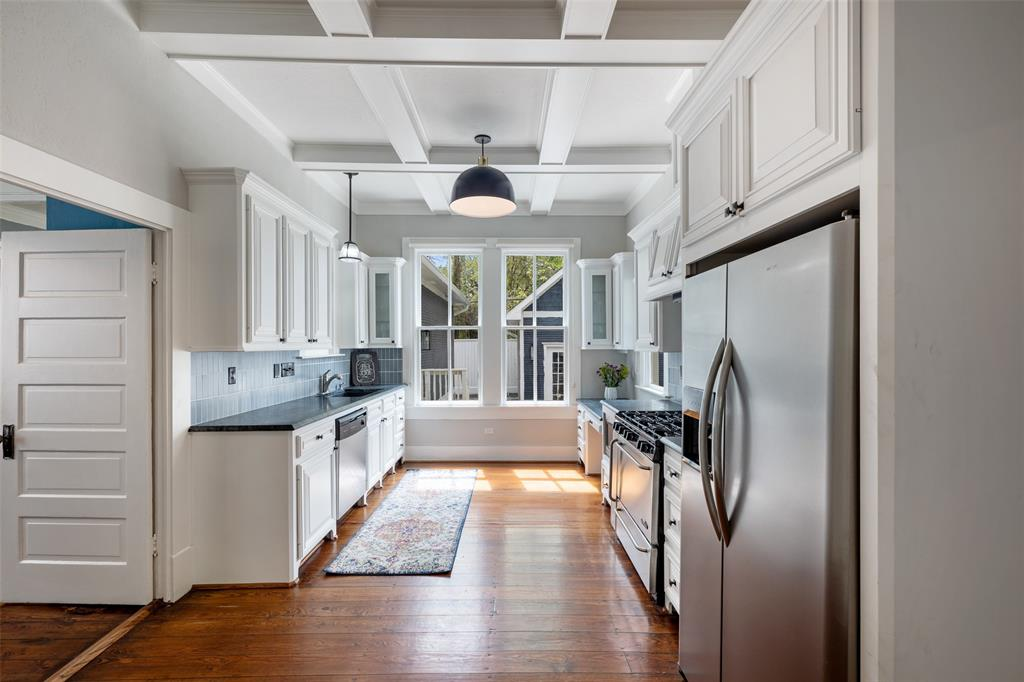 From the kitchen doorway, large windows looking into the back yard, soapstone countertops and open space for cooking or adding an island.
