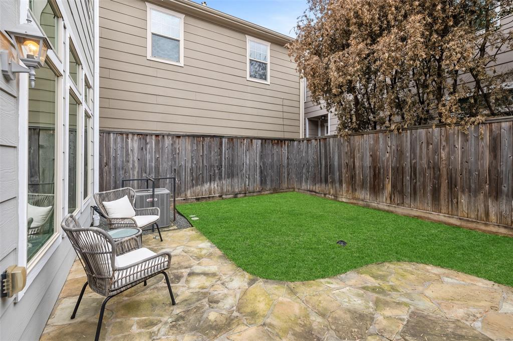 The backyard is a great space to walk the kids or the dogs run around. It includes a wonderful green space and stone patio.