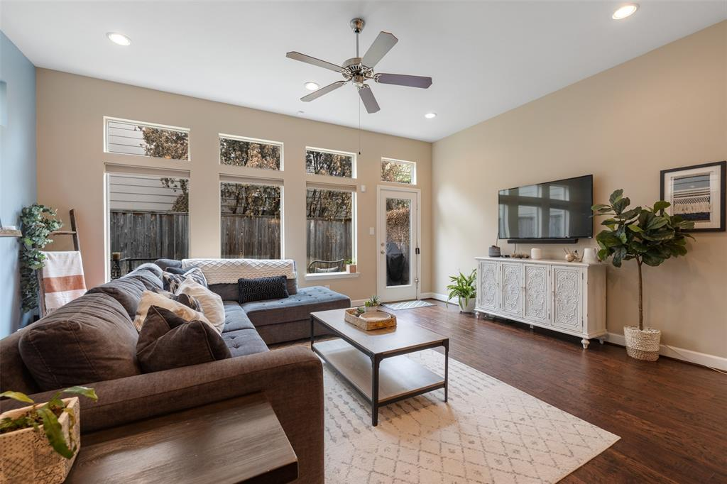 The living room, and the entire first floor living space, includes hardwood floors, and large windows that open to the backyard.