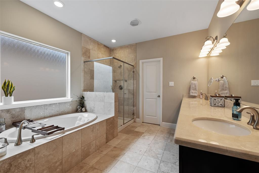 The large spa-like master bathroom incudes travertine floors, a jetted tub, and a large separate shower.